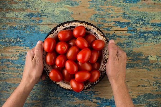 Tomates mûres dans une plaque de métal sur une table en bois Photo Premium