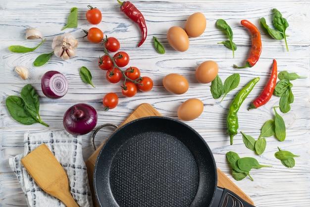 Tomates, oeufs, oignons, épinards et poivrons biologiques frais sur une table en bois avec une poêle à frire Photo Premium