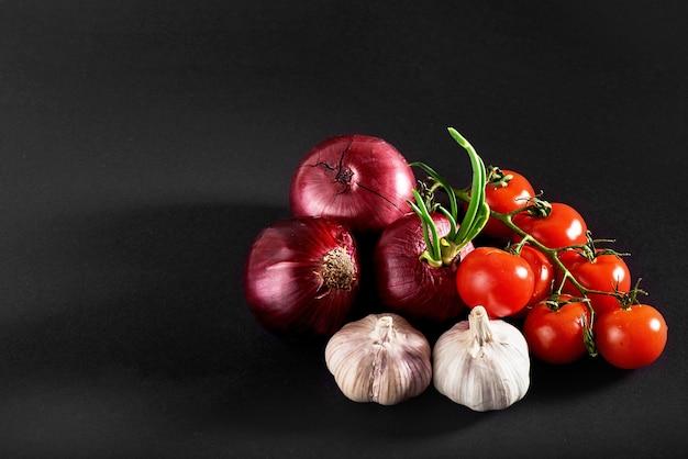 Les Tomates, Les Oignons Et L'ail Sont Isolés Sur Un Fond Noir Photo gratuit