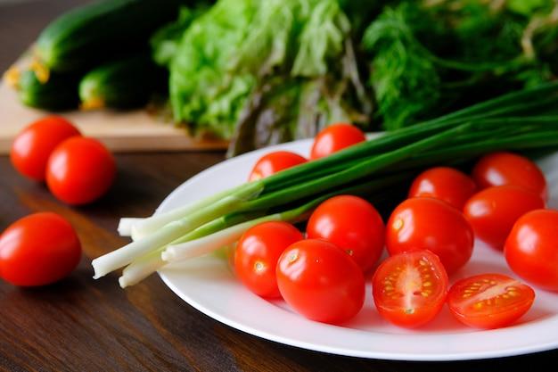 Tomates et oignons verts sur une assiette Photo Premium