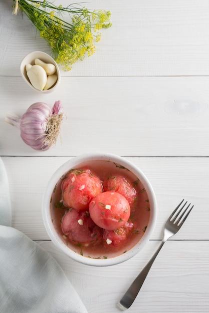 Tomates pelées marinées à l'ail et à l'aneth, fraîches et prêtes à servir. Photo Premium