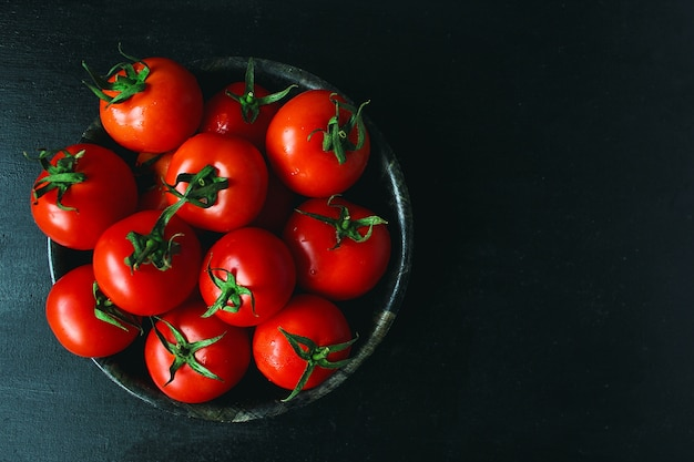 Tomates rouges biologiques fraîches en plaque noire, gros plan, concept santé, vue de dessus Photo gratuit