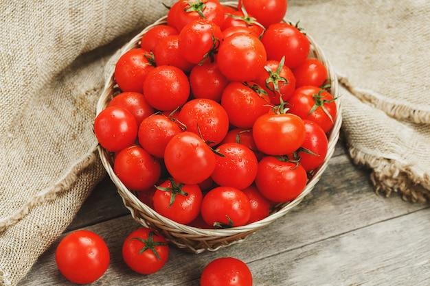Tomates rouges fraîches dans un panier en osier sur une vieille table en bois. tomates cerises mûres et juteuses avec des gouttes d'humidité, table en bois gris, autour d'un chiffon de toile de jute. dans un style rustique. Photo Premium