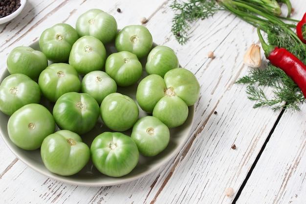 Tomates vertes, cornichons sur table en bois blanc avec poivrons verts et rouges et, piments forts, fenouil, sel, poivre noir, ail, pois, gros plan, concept santé, vue de dessus, flat lay Photo gratuit