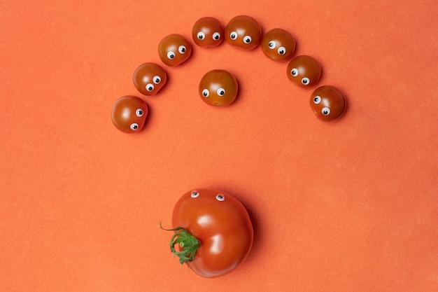 Tomates avec des yeux concept drôle, espace de copie. petite cerise fraîche et grande serre Photo Premium