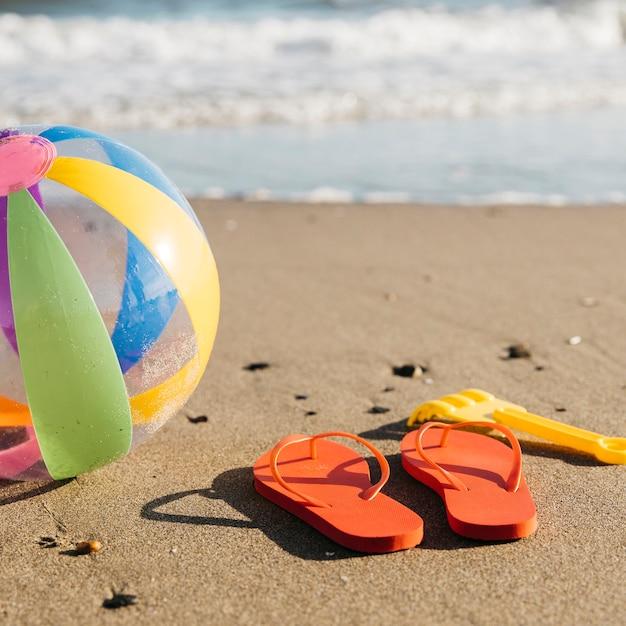 Tongs et ballon gonflable dans le sable à la plage Photo gratuit