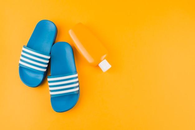 Tongs bleus avec bouteille de lotion écran solaire sur fond jaune Photo gratuit