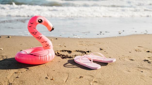 Tongs et flamants gonflables à la plage Photo gratuit