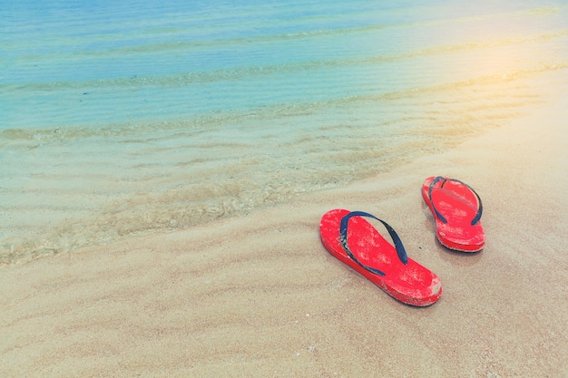 Tongs rouges sur une plage de sable fin avec forme de vague Photo Premium