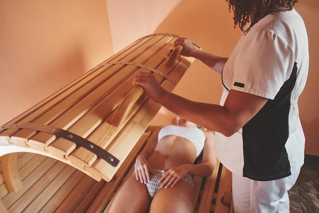 Tonneau Phyto En Bois, Sauna Horizontal. Belle Femme Massothérapeute Appliquant Un Traitement Spa à Une Jeune Femme Dans Une Salle De Bien-être Photo Premium