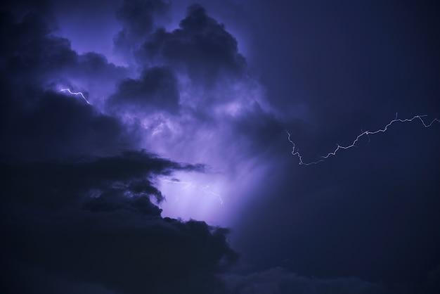 Le tonnerre éclaire le mauvais temps, le ciel bleu et les nuages noirs. Photo Premium
