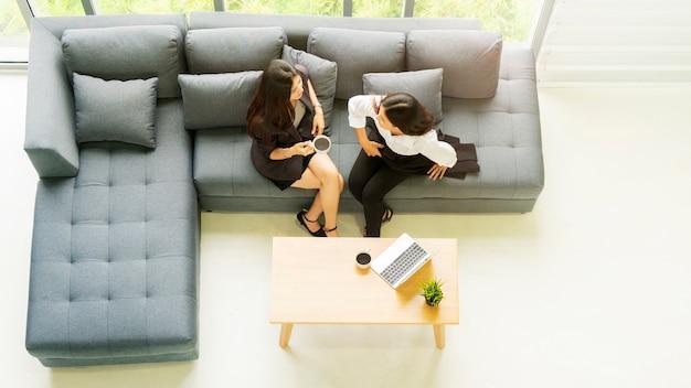 Top femme d'affaires vue aérienne parler et s'asseoir sur le canapé canapé gris avec le café noir à boire. Photo Premium