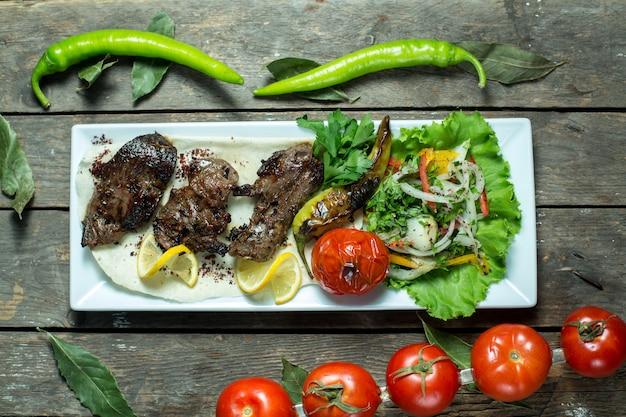 Top Kebab De Boeuf Servi Avec Oignons Tomates Grillées Et Poivre Sur Plateau Photo gratuit
