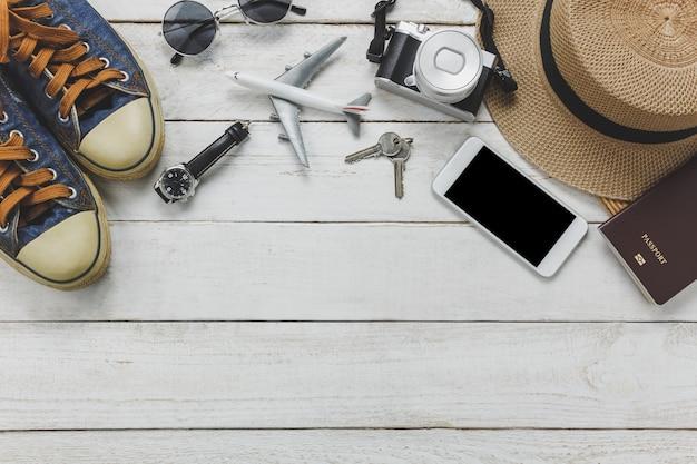Top view accessoires pour les femmes au concept de voyage. téléphone portable, avion, chapeau, passeport, montre, lunettes de soleil sur table en bois. Photo gratuit