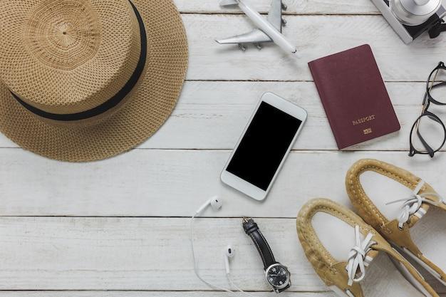Top view accessoires pour les femmes au concept de voyage. téléphone portable, avion, chapeau, passeport, montre, lunettes sur table en bois. Photo gratuit