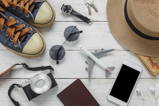 Top view accessoires pour les femmes pour le concept de voyage.white téléphone mobile et casque sur fond en bois.airplane, chapeau, passeport, montre, lunettes de soleil sur la table en bois. Photo gratuit
