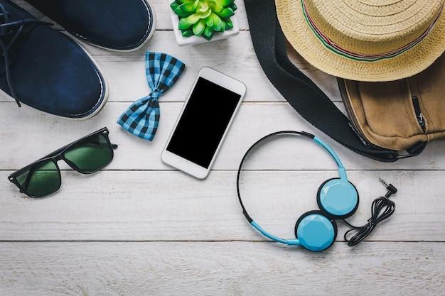 Top view accessoires pour voyager avec le concept d'habillement homme. téléphone portable et casque sur fond en bois. cravate, portefeuille, lunettes de soleil, chaussure, sac et chapeau sur table en bois. Photo gratuit
