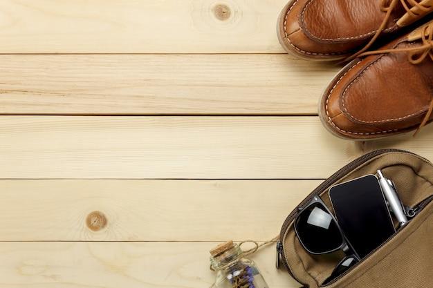 Top view accessoires voyage avec fleur, chaussure, téléphone mobile, lunettes de soleil, sac sur table en bois avec copie space.travel concept. Photo Premium