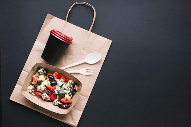 Top view box avec salade et tasse à café Photo gratuit