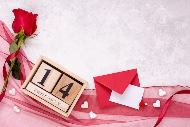 Top view decoration avec rose et enveloppe Photo gratuit