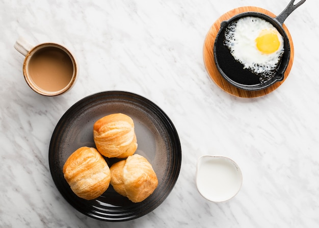Top vue collection d'oeufs de petit déjeuner dans une casserole à côté du pain Photo gratuit