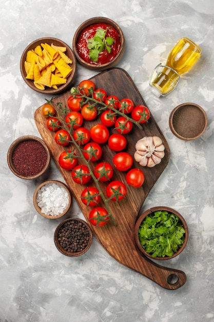 Top Vue Lointaine Tomates Cerises Fraîches Avec Assaisonnements Et Verts Sur Surface Blanche Photo gratuit