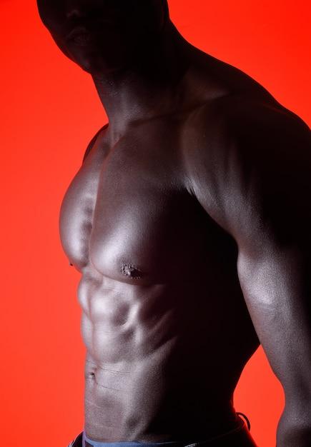 Torse d'un homme africain sur fond rouge Photo Premium