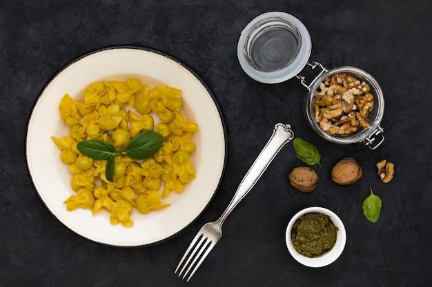 Tortellini cuits avec des feuilles de basilic et des ingrédients sur fond noir Photo gratuit