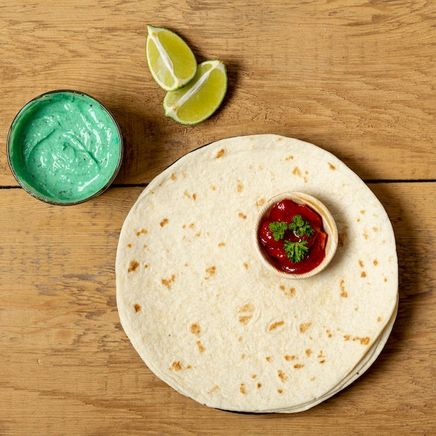 Tortilla avec diverses sauces et citron vert Photo gratuit