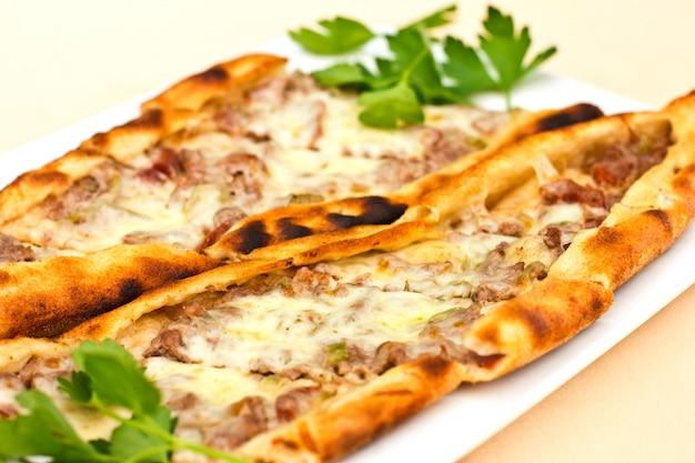 Tortilla pita turque avec des morceaux de viande, du fromage fondu et des tranches de légumes Photo Premium