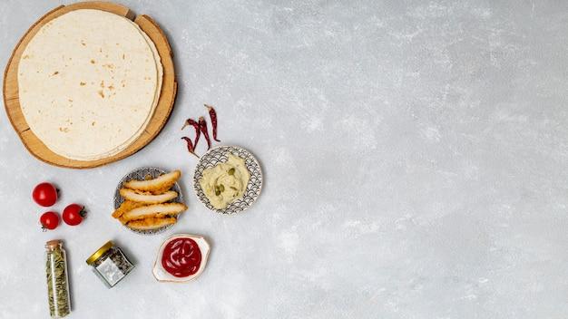 Tortilla ronde avec trempettes à côté du poulet rôti Photo gratuit