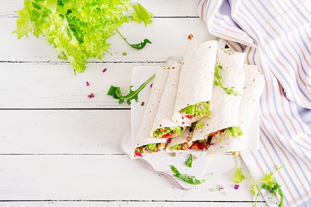 Des tortillas de fajita mexicaines dans des plats de rue enveloppent un filet de poulet grillé et des légumes frais. vue de dessus Photo Premium