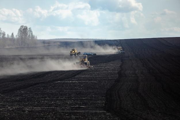 Tôt le matin, plusieurs tracteurs labourent la terre dans de grands champs Photo Premium