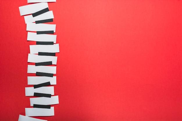 Touches de piano faites avec du papier noir et blanc sur fond rouge Photo gratuit