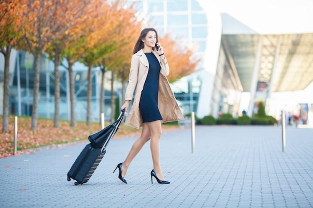 Toujours En Mouvement. Femme Qui Marche à L'aéroport Et Parle Au Téléphone Mobile Photo Premium