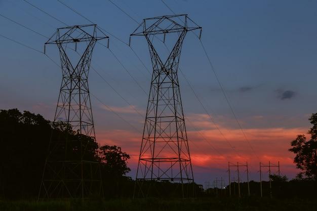 Tour de transmission de puissance se découpant contre la lueur du coucher du soleil Photo Premium