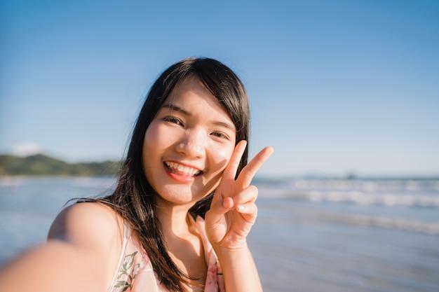 Tourisme asiatique femme selfie sur la plage, jeune belle femme heureuse souriant à l'aide de téléphone portable prenant selfie Photo gratuit