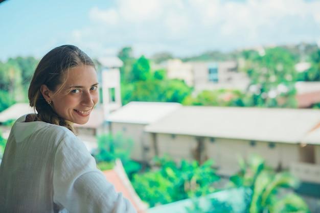 Tourisme, loisirs est une belle fille aux cheveux longs, se prélassant dans la robe blanche sur le balcon de l'hôtel avec vue sur les plantes tropicales et un petit bâtiment Photo Premium
