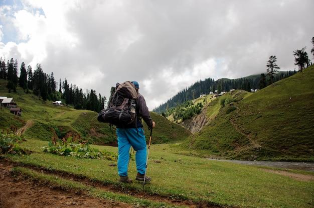 Tourisme mâle avec sac à dos se dresse près de la rivière Photo Premium