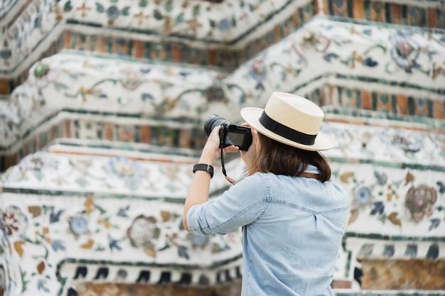 Touriste belle femme tenue de caméra pour capturer les souvenirs. temple wat arun en thaïlande. Photo Premium