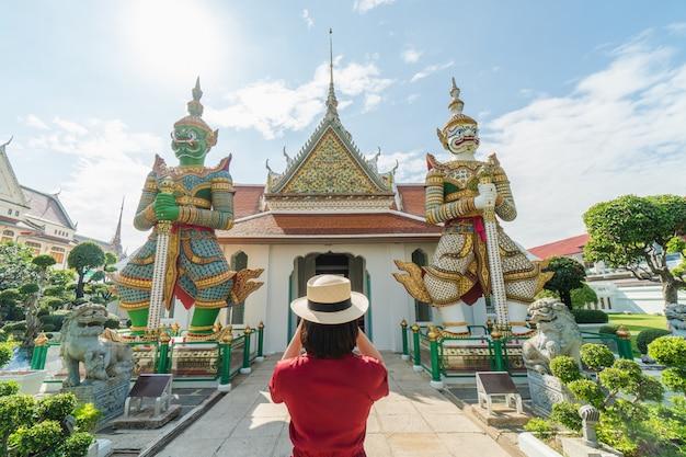 Touriste belle femme tenue de caméra pour capturer les souvenirs. temple wat arun Photo Premium