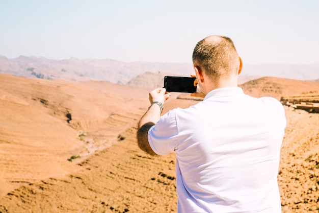 Touriste dans le paysage désertique Photo gratuit