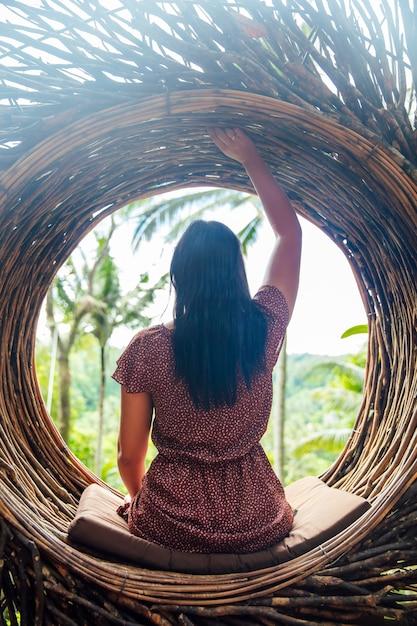 Une touriste est assise sur un nid de gros oiseau sur un arbre de l'île de bali Photo Premium