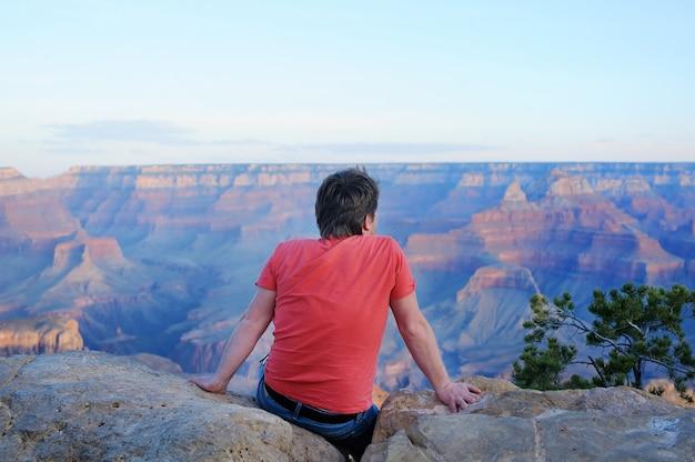Touriste homme d'âge mûr assis sur une pierre et à la recherche du grand canyon de mather point Photo Premium