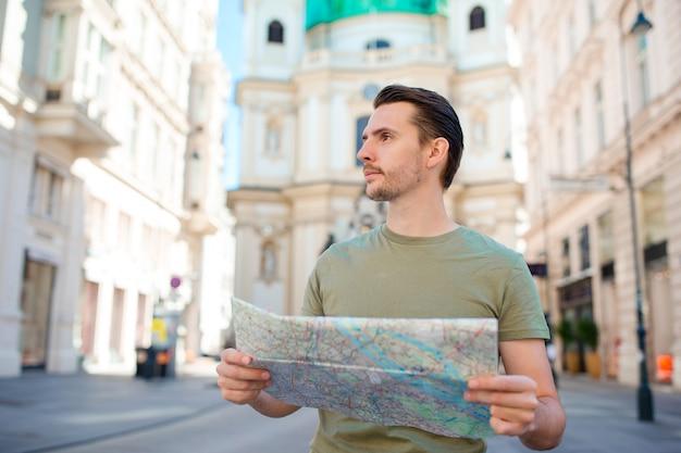 Touriste homme avec une carte de la ville et sac à dos dans la rue de l'europe. Photo Premium
