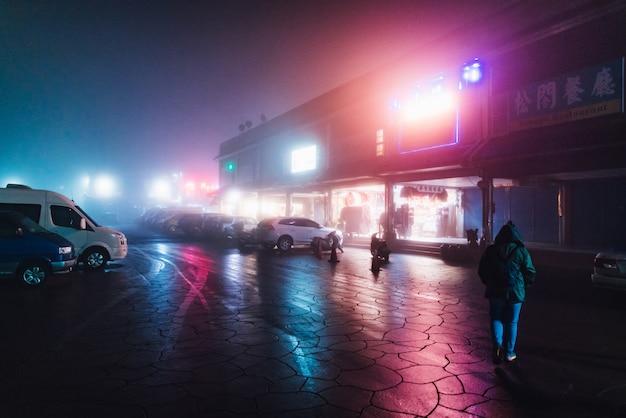 Touriste Marchant Dans La Rue Dans La Nuit Avec Le Brouillard Et Les Lumières Colorées De La Construction En Hiver à Alishan, Taiwan. Photo Premium