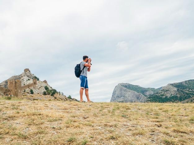 Touriste photographiant le paysage le jour de la nature sur un sac à dos professionnel Photo Premium