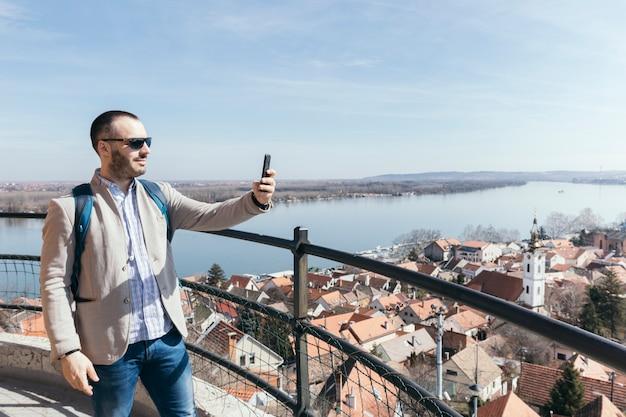 Touriste prenant des photos avec un smartphone Photo gratuit