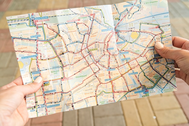 Touriste tenant une carte dans la rue Photo gratuit