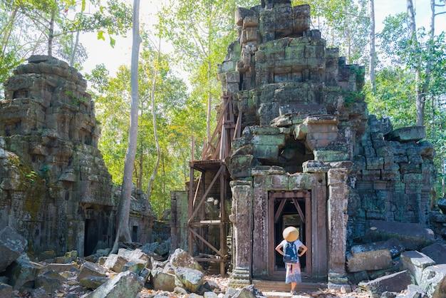 Un touriste visitant les ruines d'angkor au milieu de la jungle Photo Premium